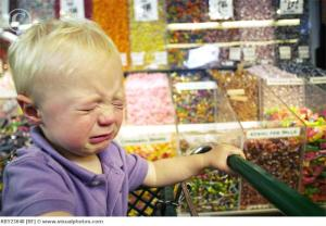 Toddler boy crying in candy aisle of grocery store
